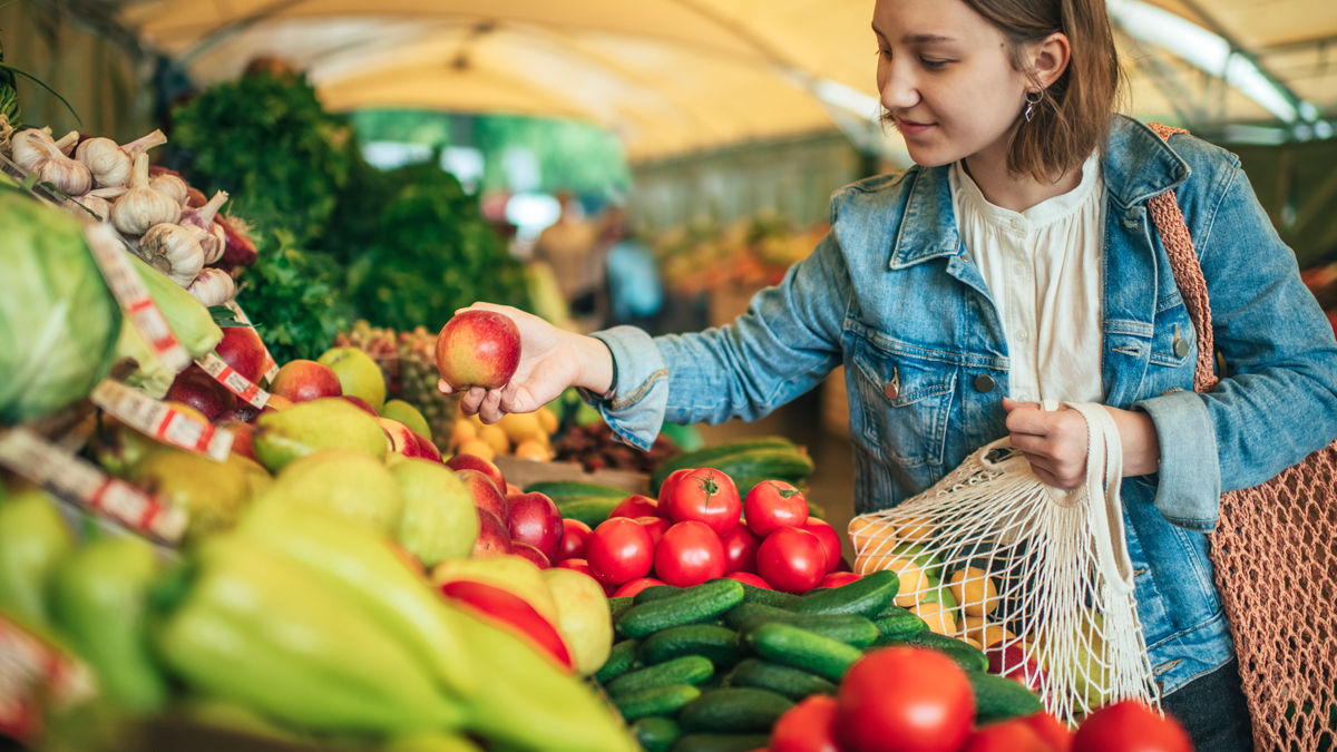 woman buying fresh vegetables with reusable shopping bag because she is vegan for the environment