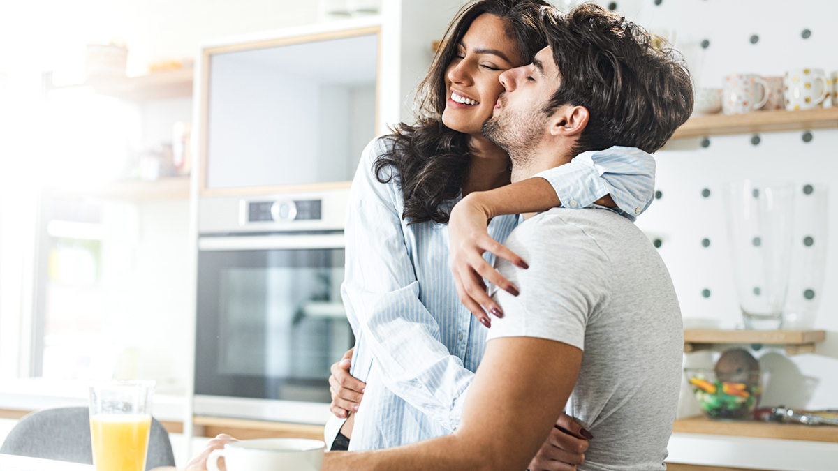 Woman who uses Kiss My Face products get a smooch in the kitchen by husband