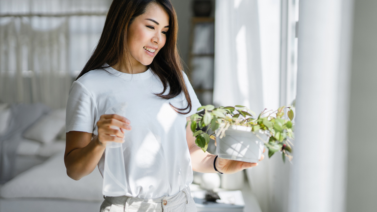 5 reasons spring cleaning is good for you includes stress reduction like this woman smiling near window enjoying the simplicity of decluttered living