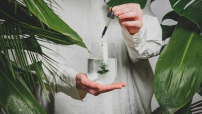 non-descript person wearing flowy white linen shows how to make chlorophyll water with drops in a glass