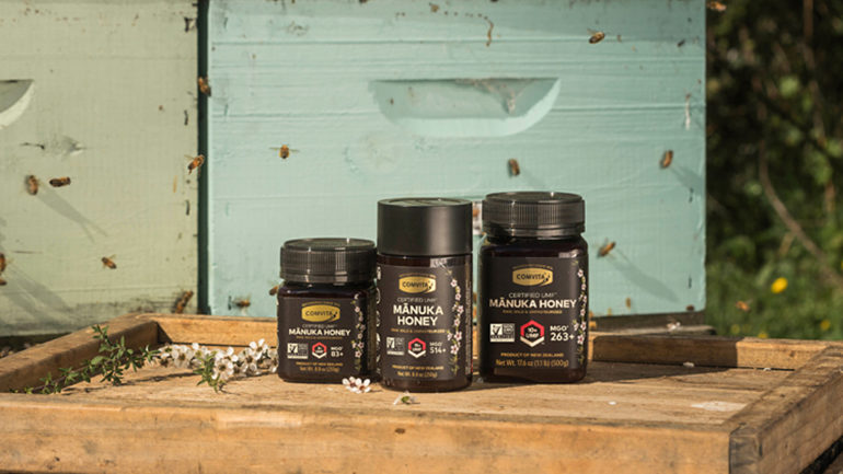 Manuka Honey Benefits are explained by Comvita whose products are shown near beekeeping supplies, bees, and manuka flowers