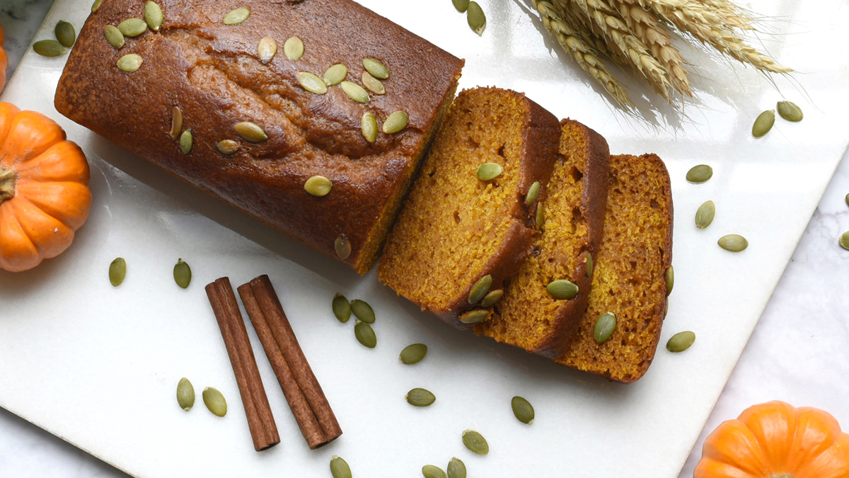 healthy pumpkin bread shown on table with cinnamon stick and pumpkin seeds